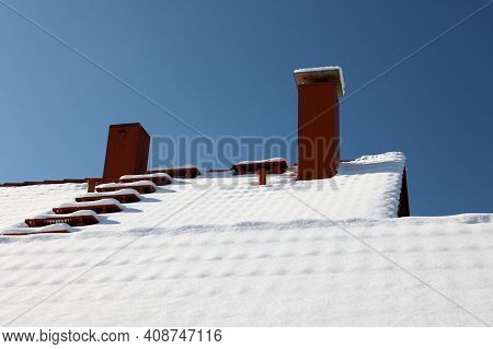 The Roof With A Chimney Is Covered With Snow In Winter