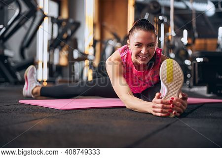 Happy Young Woman Training Flexibility In Gym