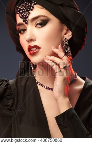 Close up portrait of a beautiful oriental woman with traditional make-up, black hijab and jewelry on a black background. Arabian beauty, fashion. Make-up and cosmetics.
