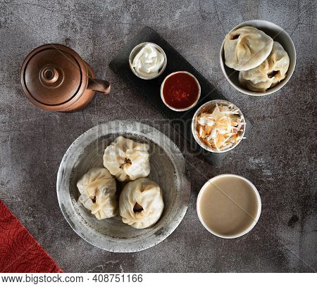 Traditional Dishes In Buryatia-buuz, Minced Meat In Dough, On A Ceramic Plate And In A Bowl, Green T