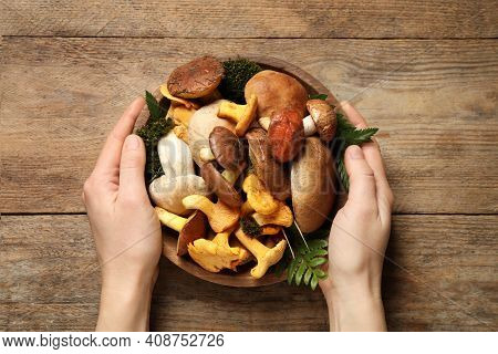 Top View Of Woman Holding Bowl With Different Wild Mushrooms On Wooden Background, Closeup
