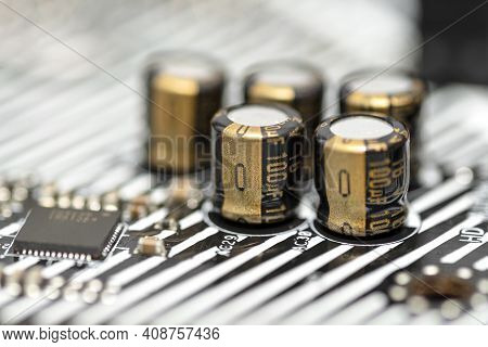A Macro Shot Of Five Capacitors In A Metal Housing, Soldered To The Motherboard Of A Desktop Compute