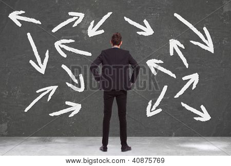 Business man with lots of choices does not know which way to go