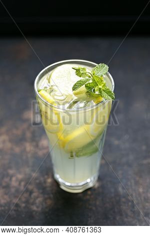 A Close-up Of Glass Of Lemonade With Ice Cubes, Mint Sprig, Lemon Slices. Yellow Drink, Cocktail, On