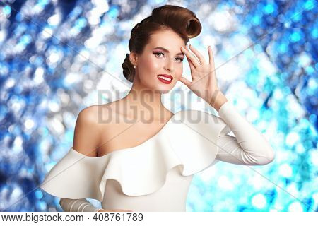 Charming smiling lady in elegant white dress. Pin-up style in clothes, hair and make-up. Festive look.