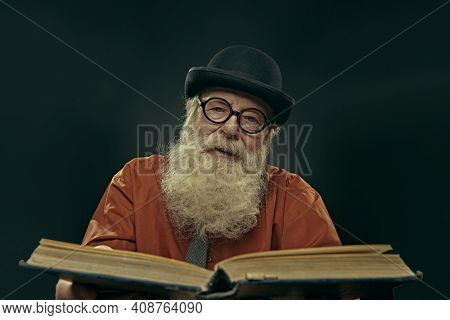 An intelligent old man in glasses and bowler with a long gray beard holds an old big book and looks at the camera. Old age wisdom.