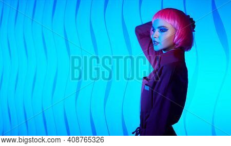 Fashion beauty trends. Portrait of a gorgeous young woman with bright glitter makeup and pink hair posing in mixed color neon light. Makeup cosmetics and hairstyle. Copy space.