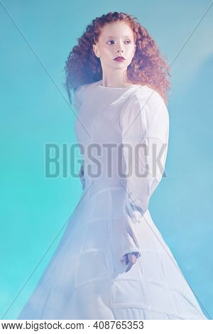 Art and fashion. Portrait of a refined fashion model girl with lush red curly hair posing in a white haute couture dress. Studio shot.