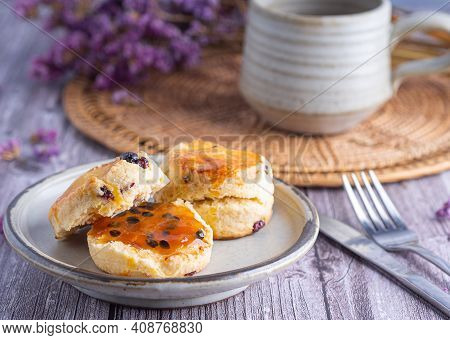Close-up Of Traditional British Scones Placed On A Plate With A Teacup And Flower Blurred Background