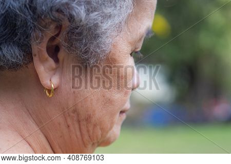 Side View Of The Face Of A Senior Woman Wearing A Golden Earring. Concept Of Aged People And Healthc