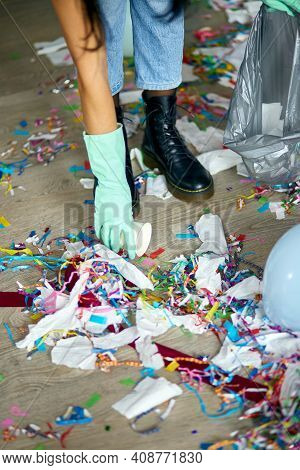 Woman Cleaning Mess Of Floor In Room After Party, Removes Garbage From The Floor