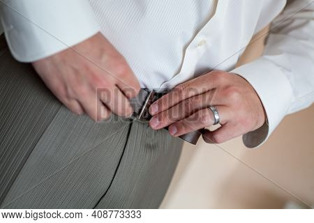 A Man In Pants And Shirt Buttoned A Black Leather Trouser Belt. Groom Dress Up A Belt With Buckle. B