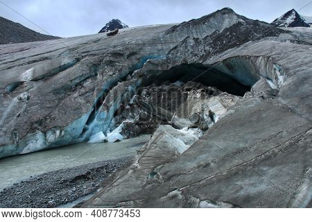 Big Sophia Glacier In Altai With Huge Cracks And A Cave, Close, Pieces Of Ice, Stones, A River Flows