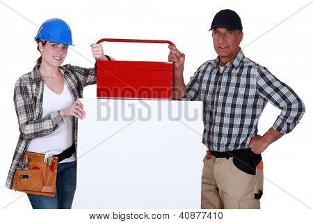 Tradespeople posing with their toolbox and a blank sign