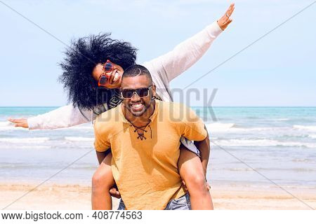 African American Happy Couple Having Fun Piggyback Riding And Playing Airplane On The Beach - Black