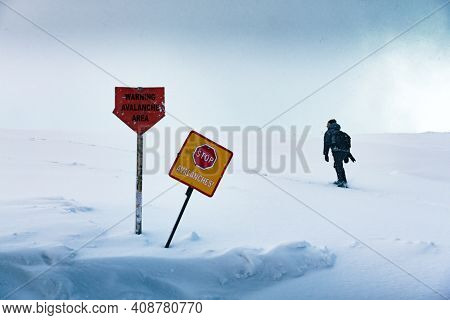 The tourist enters the forbidden dangerous zone of the avalanche in winter time. Warning signs in snow in the foreground. Avalanches danger concept