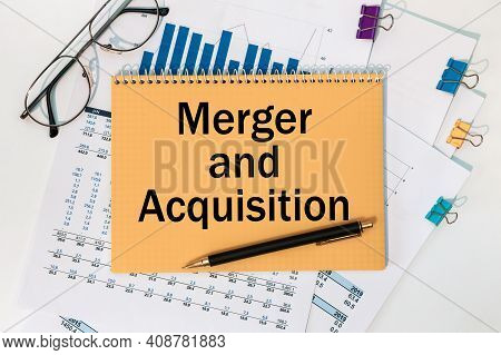 Notebook With The Text Merger And Acquisition On The Office Table Among The Stationery.