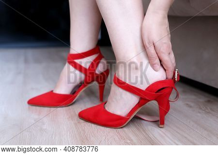 Foot Pain, Woman Massaging Her Heel And Ankle By Hand. Female Legs In Red Shoes On High Heels On The