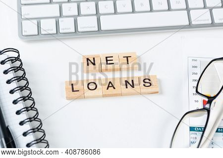 Net Loans Concept With Letters On Cubes. Still Life Of Office Workplace With Supplies. Flat Lay Whit