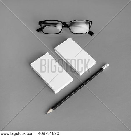 Blank Branding Identity Set On Gray Paper Background. Business Cards, Pencil And Glasses. Corporate