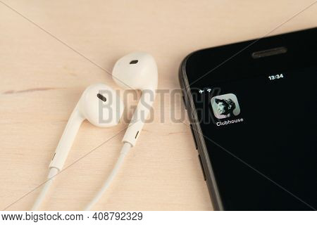 Minsk, Belarus - February 18, 2021: Clubhouse application logo close-up. Mobile phone on the wooden table with open Clubhouse drop in audio chat app and set of headphones. Shallow depth of field