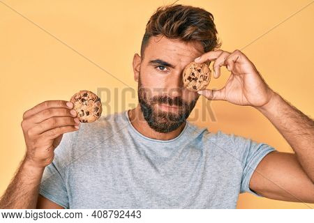 Young hispanic man holding cookie relaxed with serious expression on face. simple and natural looking at the camera.