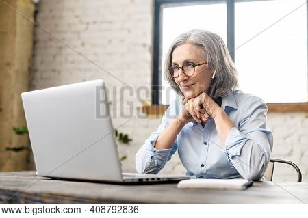 Intelligent Elderly Gray-haired Businesswoman Using A Laptop In The Office. Smart Mature Woman Entre