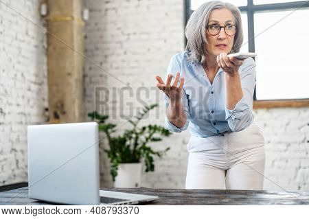 Busy Elderly Business Woman In Eyewear Using Voice Recognition App On The Phone. Modern Aged Female