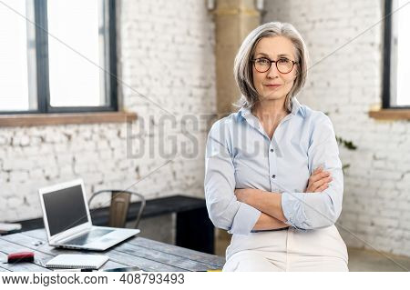 Serious And Strict Old Senior Business Woman Wearing Smart Casual Shirt And Stylish Eyeglasses Stand