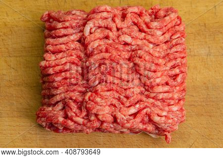 Red Minced Beef With Chunks Of Fat On A Chopping Board. Top View