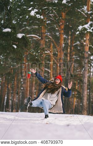 Girl Slipped On The Wet Snow In The Forest. Paper Cup Flew Out Of Hand. The Moment Before The Fall