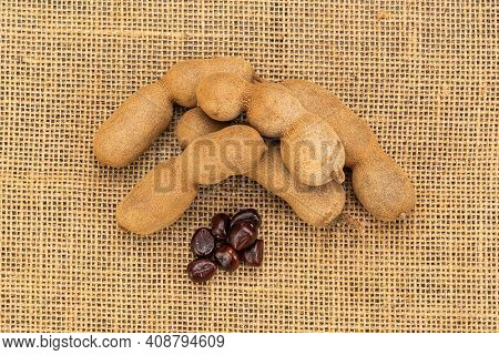 Top View Of Ripe Tamarind And Seeds On Sackcloth. Tamarind Is A Kind Of Herbs Use In Spa.