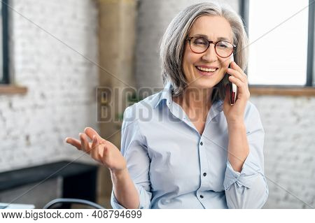 Smiling And Positive Senior Businesswoman Talking By The Smartphone In The Modern Office. An Elderly
