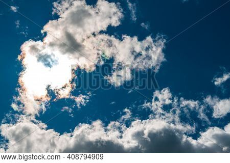 Bizarre Clouds Against A Blue Sky. Whimsical Clouds Against The Sun.