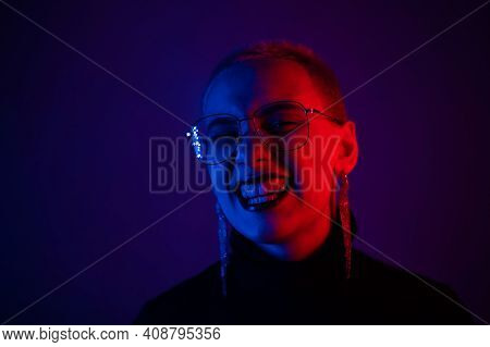 Portrait Of A Beautiful Young Woman With Short Hair In Neon Light. The Girl Is Posing And Grinning