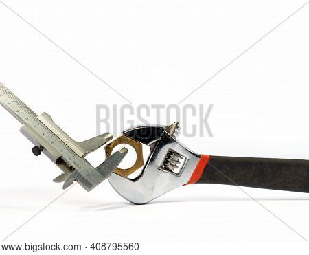 Adjustable Wrench, Caliper And Nut On A White Background.