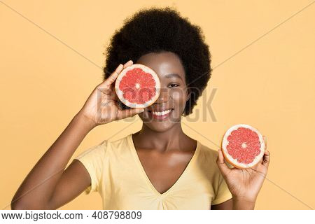 Close-up Portrait Of Charming African Girl Holding Halfs Of Grapefruit, Hiding Her Eye. Amazing Smil