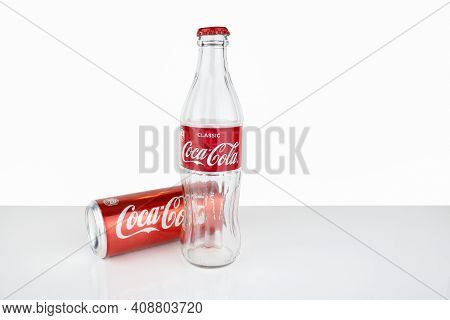 Empty Glass Bottle And Tin Can Of Coca Cola In Red Design On White Surface, Lying Tin Can. - Russia,