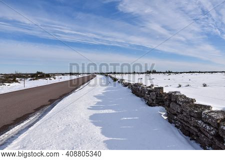 Country Road In A Plain Landscape In Winter Season On The Island Oland In Sweden