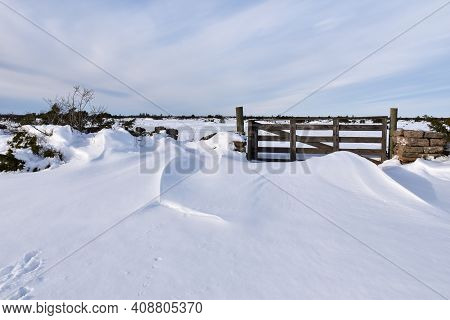 Snowdrift By An Old Wooden Gate Into A Wide Open Plan Landscape