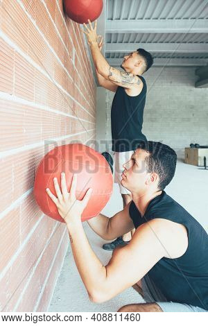 Side View Of A Pair Of Young Fit Men Doing Wall Ball Exercises At The Gym. Workout Routine. Healthy