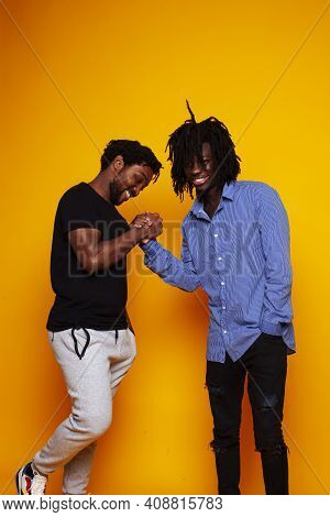 Two African American Guys Posing Cheerful Together On Yellow Background, Lifestyle People Concept