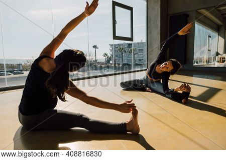 Prenatal Personal Trainer Teaching Stretch To A Pregnant Woman On The Floor Of A Spacious Fitness Ce
