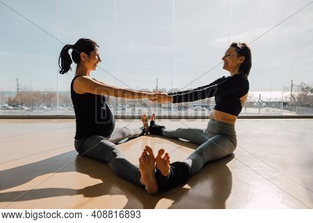 Young Women Working Out In Gym, Doing Stretching Exercise In The Morning Sunlight. Smiling Pregnant