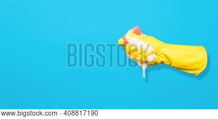 Flying Yellow Glove Squeezing Sponge For Washing With Foam, Copy Space. Foamy Gel Dripping From Red