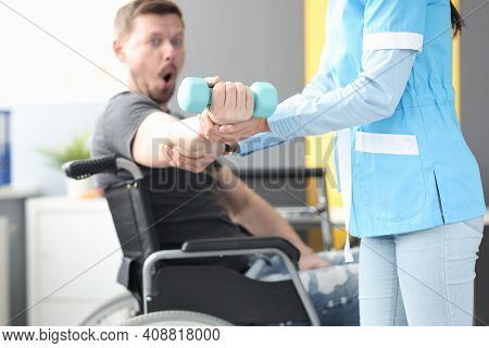 Rehabilitation Physician Helping Lift Dumbbell To Patient In Wheelchair. Medical Rehabilitation Of D
