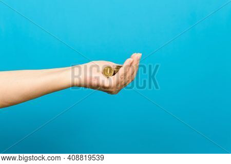Elderly Woman's Hand Holding Coins On Blue Background, Selective Focus. Saving Money Concept, Povert