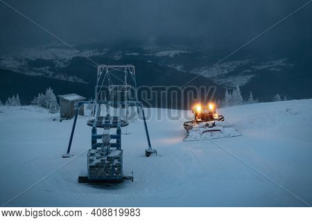 Ratrak in action on the morning ski slope. Machine for skiing slope preparations with headlights on in snowy mountains