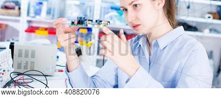 Engineer working with circuits. A woman engineer solders circuits sitting at a table.  Microchip production factory.