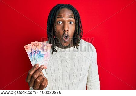 African american man with braids holding 20 swiss franc banknotes scared and amazed with open mouth for surprise, disbelief face